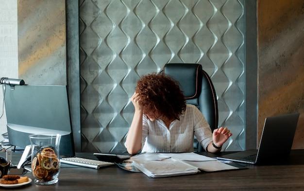 Ritratto di donna giovane lavoratore di ufficio seduto alla scrivania in ufficio con documenti e computer portatile cercando stanco e oberato di lavoro in ufficio Foto Gratuite