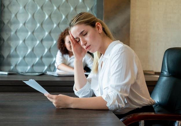 Ritratto di giovane donna di impiegato seduto alla scrivania in ufficio con documenti che sembrano annoiati e oberati di lavoro seduto in ufficio Foto Gratuite