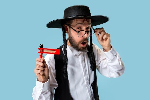 Ritratto di un giovane ebreo ortodosso con cricchetto grager in legno durante il festival purim Foto Gratuite