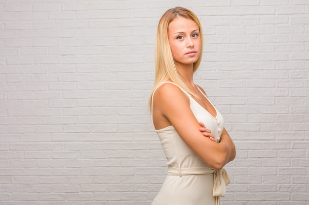 Portrait of young pretty blonde woman against a bricks wall crossing his arms, smiling and happy, being confident and friendly Premium Photo