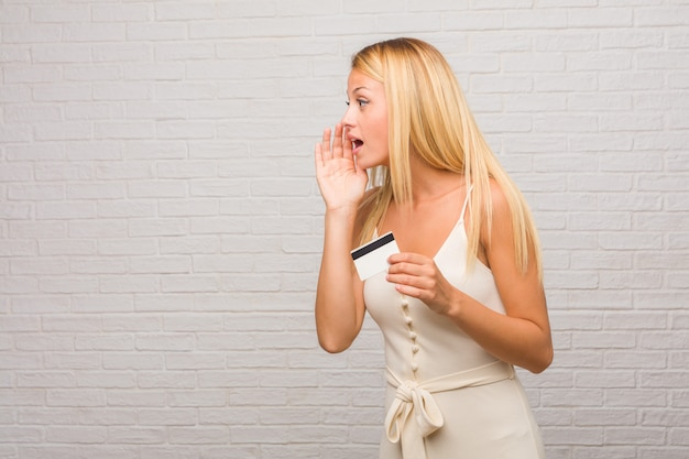 Portrait of young pretty blonde woman against a bricks wall whispering gossip undertone Premium Photo