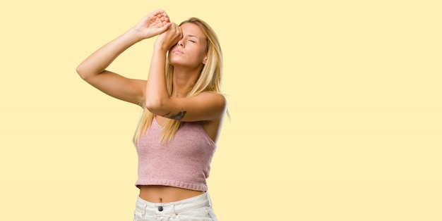 Portrait of young pretty blonde woman looking through a gap, hiding and squinting Premium Photo