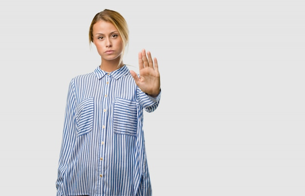 Portrait of a young pretty blonde woman serious and determined, putting hand in front, stop gesture, deny concept Premium Photo