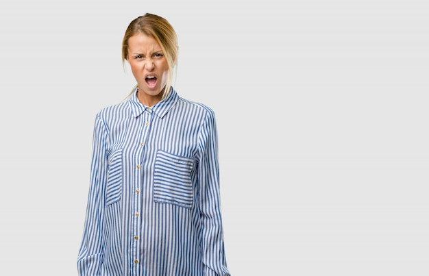 Portrait of a young pretty blonde woman very angry and upset, very tense, screaming furious, negative and crazy Premium Photo