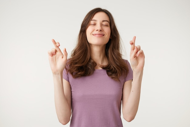 Portrait of young pretty inspired woman making a wish with crossed fingers, closed eyes, hopeful gesture Free Photo