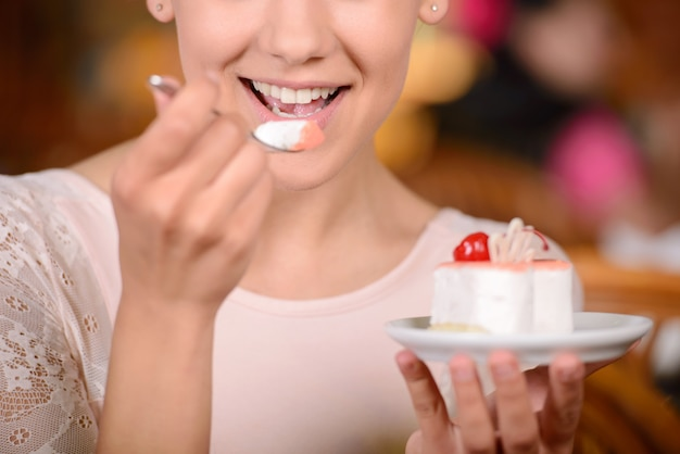 Portrait of young pretty smiling woman eating cake. Premium Photo