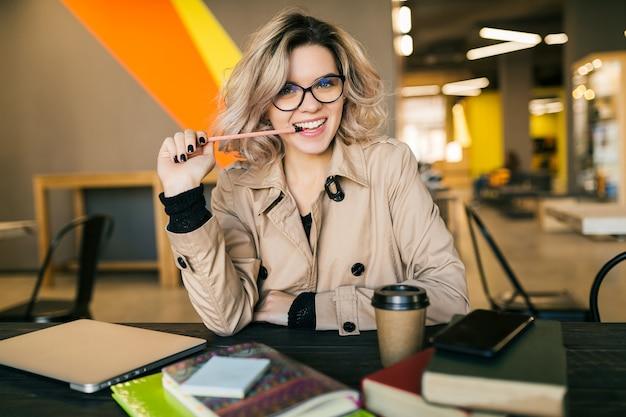 Ritratto di giovane donna graziosa che ha un'idea, seduto al tavolo in trench, lavorando sul computer portatile Foto Gratuite