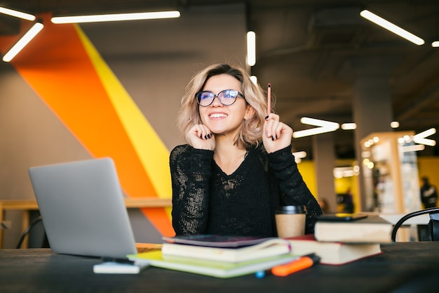 Portrait of young pretty woman sitting at table in black shirt working on laptop in co-working office Free Photo