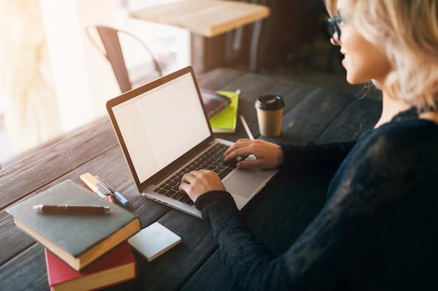 Ritratto di giovane donna graziosa che si siede al tavolo in camicia nera che lavora al computer portatile in ufficio di co-working Foto Gratuite
