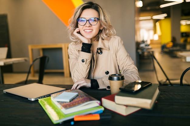 Ritratto di giovane donna graziosa che si siede al tavolo in trench, lavorando sul computer portatile in ufficio di co-working Foto Gratuite