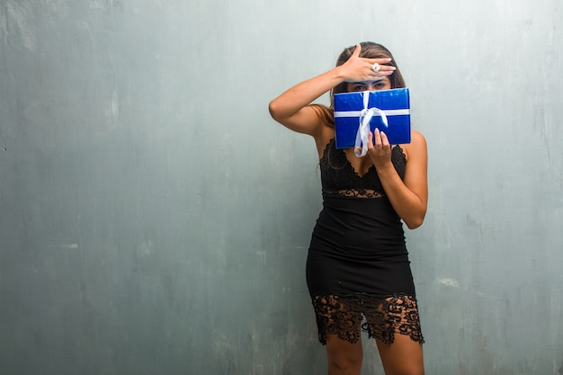Portrait of young pretty woman wearing a dress against a wall looking through a gap Premium Photo