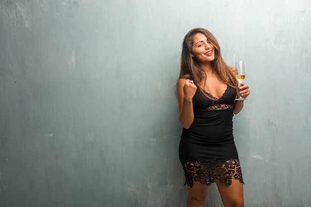 Portrait of young pretty woman wearing a dress against a wall very happy and excited Premium Photo