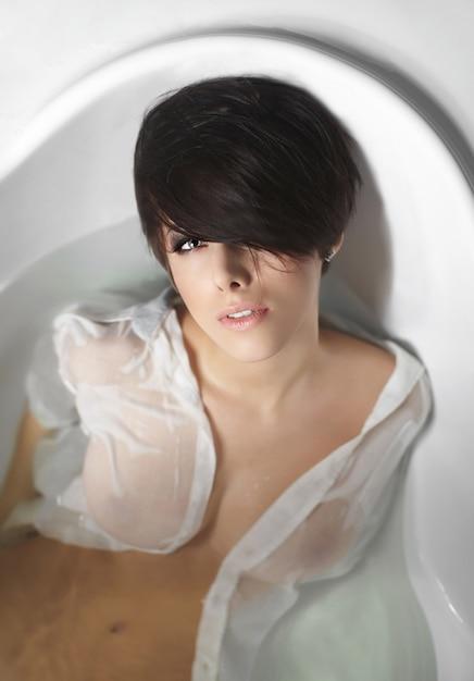 Portrait of young pretty woman with short hair enjoying in bath in white men shirt touching lips Free Photo