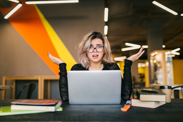 Portrait of young pretty woman with socked face expression, sitting at table working on laptop in co-working office, wearing glasses, stress at work, funny emotion, student in class room, frustration Free Photo