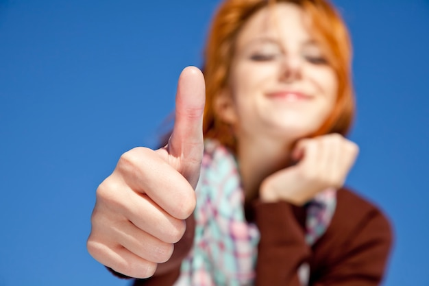 Portrait of young red-haired girl which show ok symbol on blue background. Premium Photo