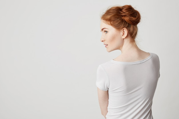 Portrait of young redhead girl with buns standing back to camera looking in side . Free Photo