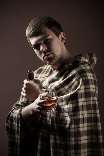Portrait of a young sad man suffering from alcoholism wrapped up in a plaid with a glass and an alcoholic bottle in his hands against a dark wall Premium Photo