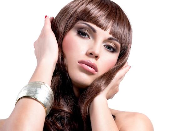 Ritratto di giovane donna sexy con lunghi capelli castani. modello di bella ragazza con bigiotteria alla moda di colore argento. Foto Gratuite