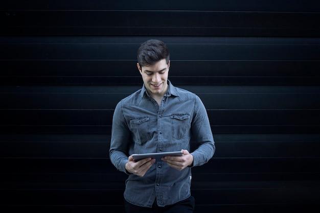Ritratto di giovane uomo bello sorridente che tiene computer tablet e guardando il display Foto Gratuite