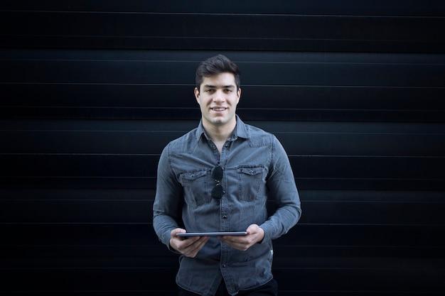 Ritratto di giovane uomo bello sorridente tenendo il computer tablet e guardando dritto in avanti Foto Gratuite