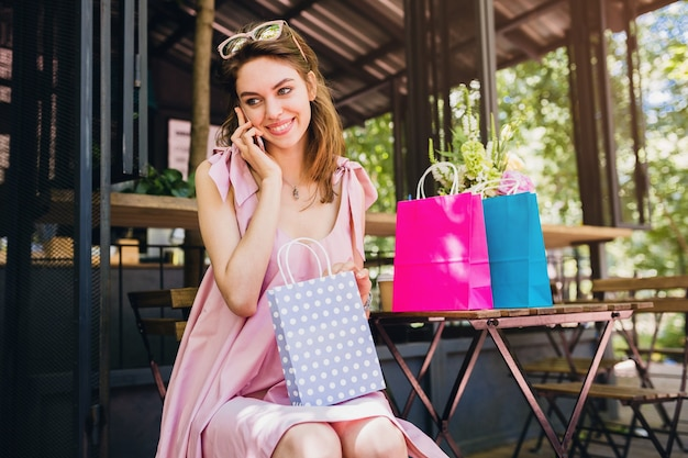 Portrait of young smiling happy attractive woman sitting in cafe talking on phone with shopping bags, summer fashion outfit, hipster style, pink cotton dress, trendy apparel Free Photo