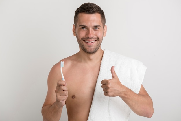 Portrait of young smiling man showing thumb up gesture while holding tooth brush Free Photo
