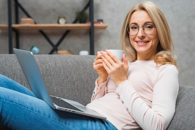 Portrait of a young smiling woman holding cup of coffee with an open laptop on her lap Free Photo