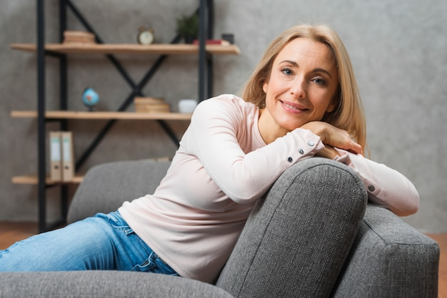 Portrait of a young smiling woman leaning on sofa at home Free Photo