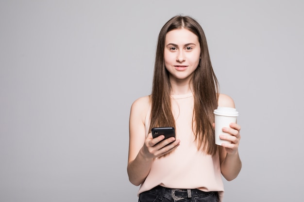 Portrait of a young smiling woman in shirt texting message on mobile phone and holding cup of coffee to go isolated over gray wall Free Photo