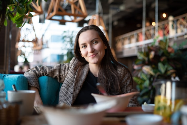 Portrait of a young smiling woman at a table in a restaurant with a blurred Premium Photo