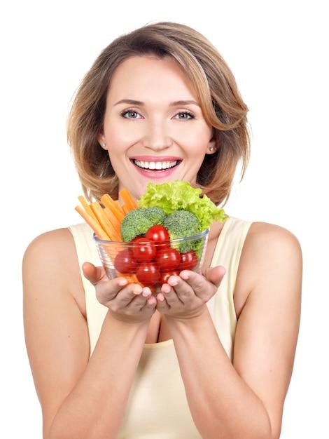 Ritratto di una giovane donna sorridente con un piatto di verdure - isolato su bianco. Foto Gratuite