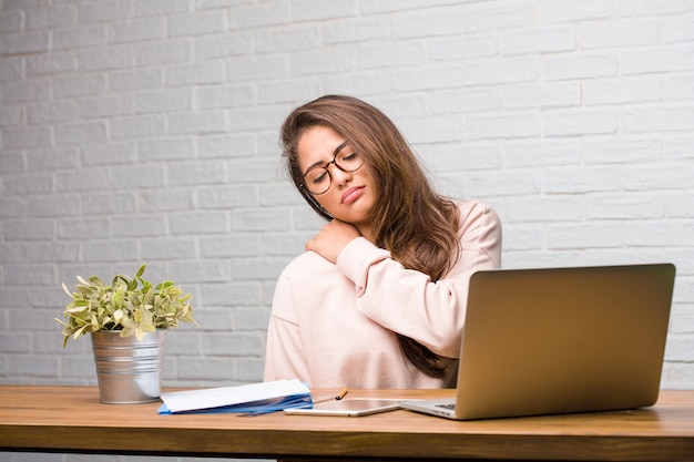 Portrait of young student latin woman sitting on her desk with back pain due to work stress Premium Photo