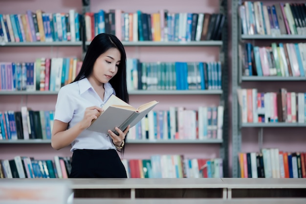 Portrait of young student reading a book in a library Free Photo