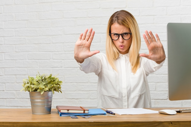 Portrait of young student sitting on her desk doing tasks serious and determined, putting hand in front, stop gesture, deny concept Premium Photo