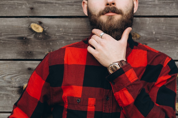 Portrait of a young stylish bearded man dressed up in jeans and a true worker black by red shirt. Premium Photo