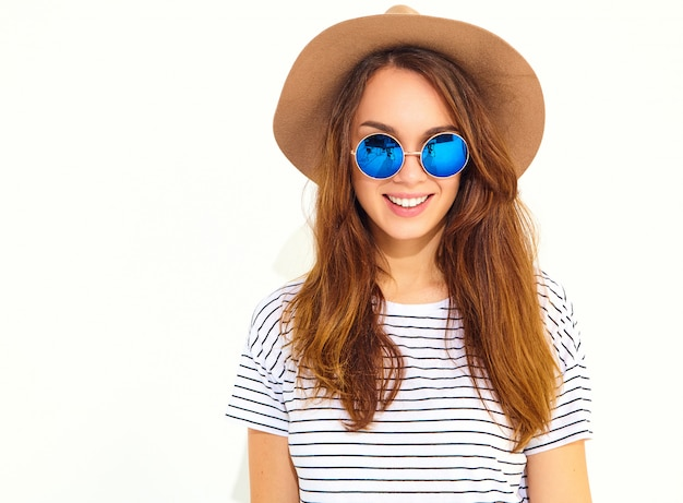 Portrait of young stylish laughing woman model in casual summer clothes in brown hat isolated on white wall Free Photo