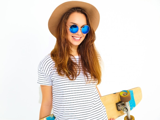 Portrait of young stylish woman model in casual summer clothes in brown hat posing with longboard desk. isolated on white Free Photo