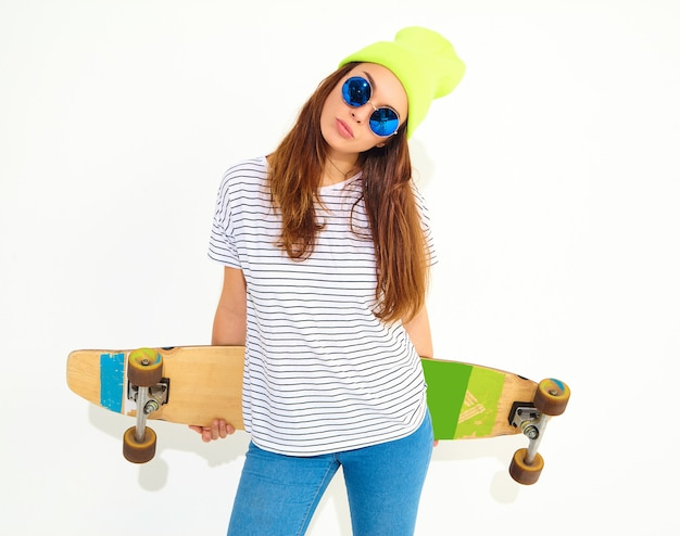 Portrait of young stylish woman model in casual summer clothes in yellow beanie hat posing with longboard desk. isolated on white Free Photo