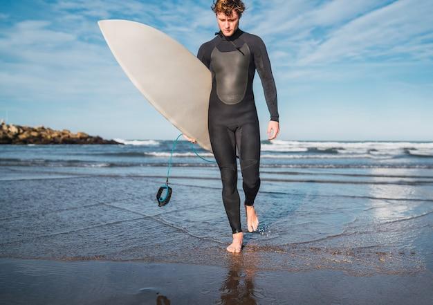 Ritratto di giovane surfista lasciando l'acqua con la tavola da surf sotto il braccio. sport e sport acquatici concetto. Foto Gratuite