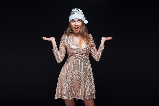 Portrait of young surprised woman in santa hat holding something on her hands. Premium Photo