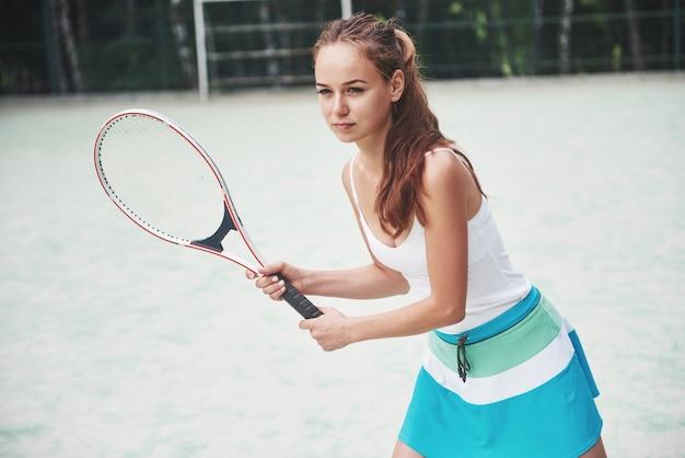Ritratto di un giovane giocatore di tennis in piedi pronto per un servizio. Foto Gratuite