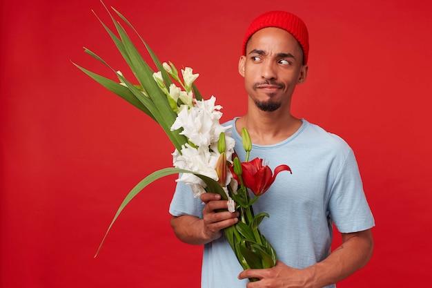 Ritratto di giovane uomo attraente pensante in cappello rosso e maglietta blu, tiene un mazzo nelle sue mani, dubitando e distoglie lo sguardo, si leva in piedi sopra il backgroud rosso. Foto Gratuite