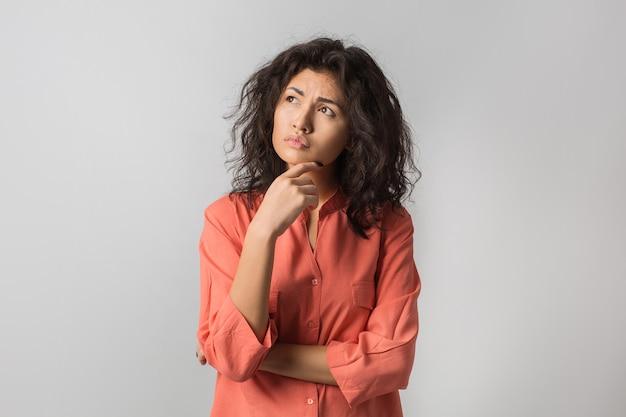 Ritratto di giovane donna castana premurosa in camicia arancione Foto Gratuite