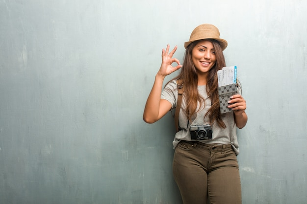 Portrait of young traveler latin woman against a wall cheerful and confident doing ok gesture Premium Photo