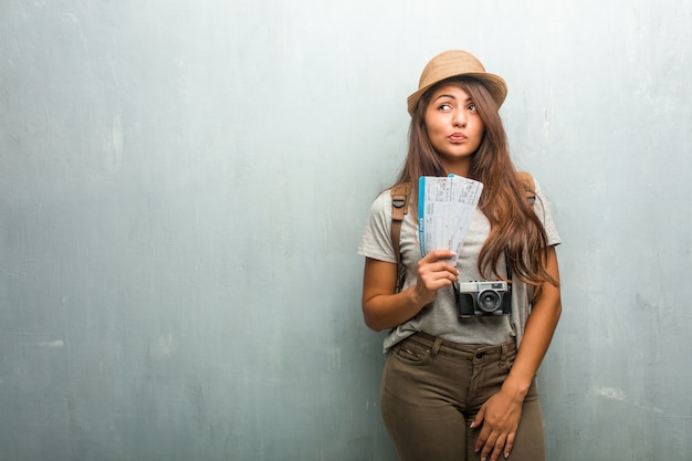 Portrait of young traveler latin woman against a wall doubting and confused, thinking of an idea or worried about something. Premium Photo