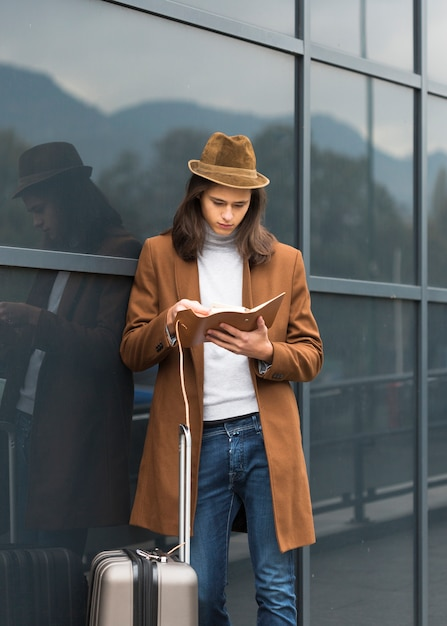 Portrait of young traveler reading Free Photo