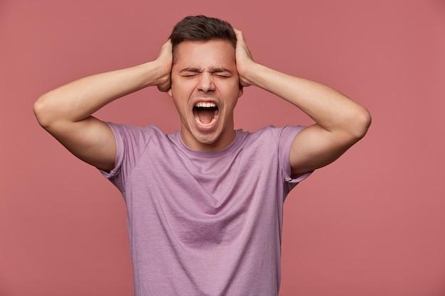 Ritratto di giovane uomo attraente infelice in maglietta vuota, sta su sfondo rosa e urlando, tiene la testa, sembra arrabbiato e infelice. Foto Gratuite