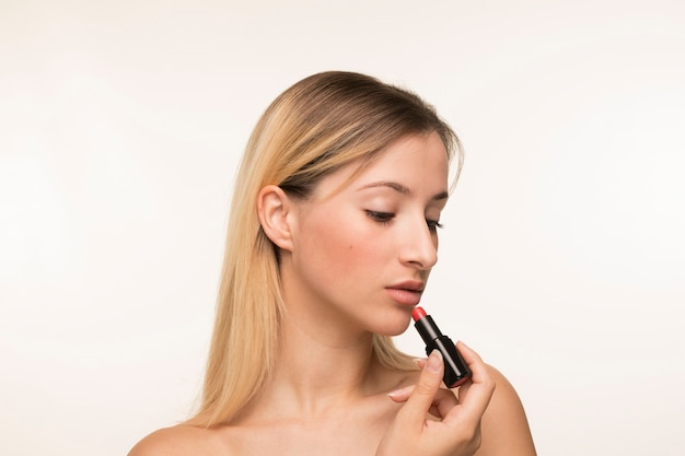 Portrait of young woman applying lipstick Free Photo
