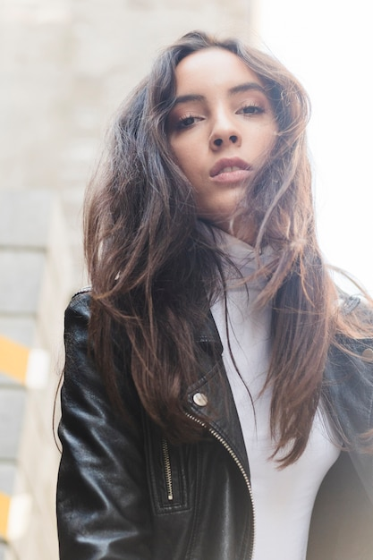 Portrait of a young woman in black leather jacket looking at camera Free Photo