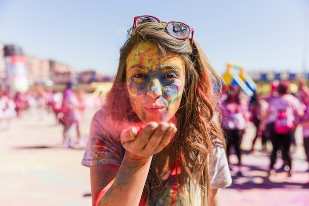 Portrait of a young woman blowing holi color in front of camera Free Photo